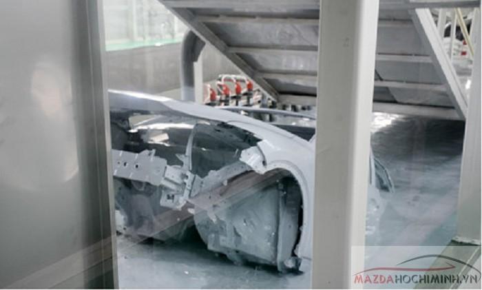 Các robot tự động sẽ lần lượt nhúng ngập hoàn toàn thân xe trong các bể chứa hóa chất